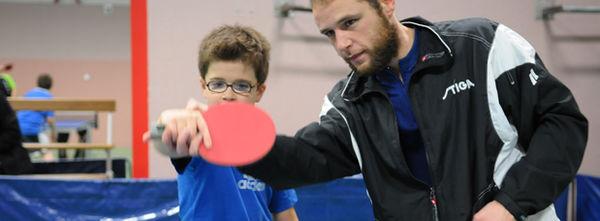 Photo d'un enfant en train d'apprendre à jouer au tennis de table